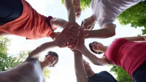 team of people with hands in the middle standing in a circle